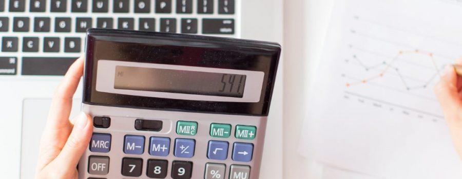 Picado mano sujetando una calculadora.